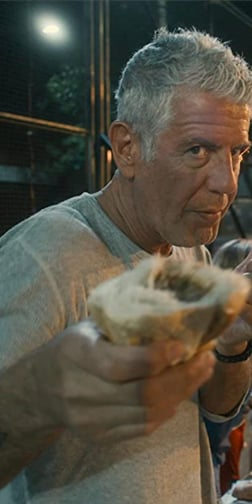 Anthony Bourdain holding food in his hand up to the camera