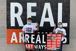 Real Art Ways student apprentices outside wearing masks holding a Real Art Ways banner