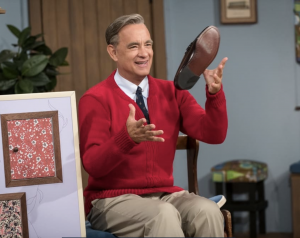An image of Tom Hanks as Mr. Rogers. He is wearing a red sweater and throwing a shoe in the air.