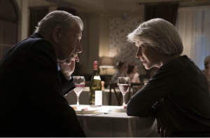 """Ian McKellen as Roy Courtnay and Helen Mirren as Betty McLeish in New Line Cinema's suspense thriller """"The Good Liar."""" Both actors are seated at a table looking each other inquisitively."""