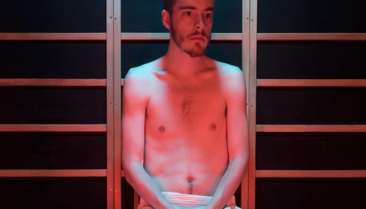 An image of Julian seated in an infrared sauna.  His hands are folded in his lap and he is bathed in warm light.