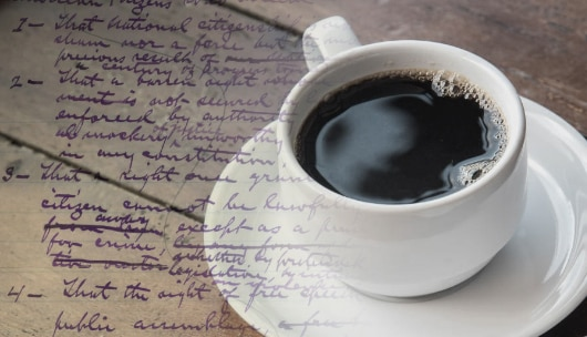 A cup of coffee on a table with handwriting overlaid.