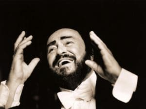 Pavarotti with his arms raised in the air, smiling.
