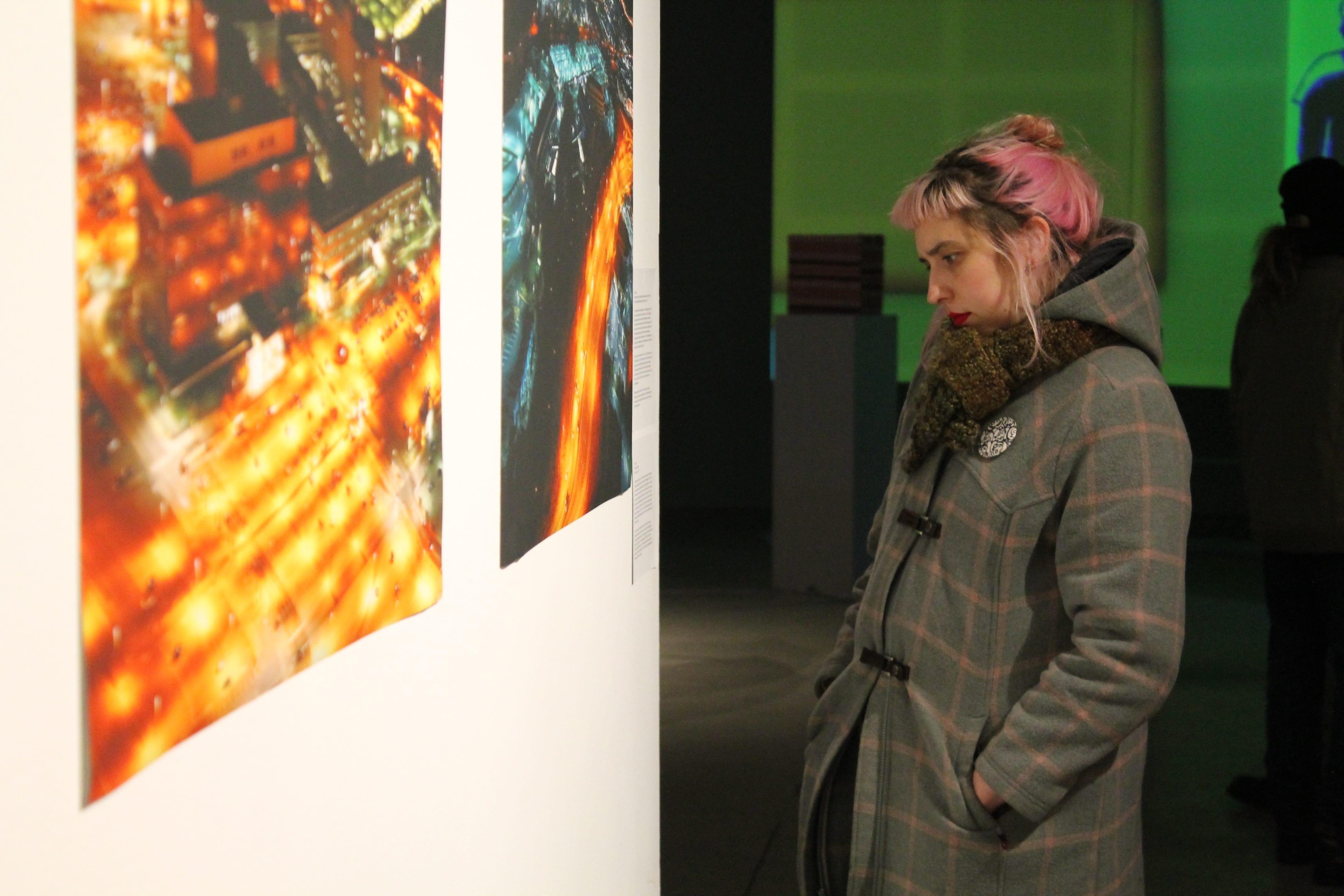 A woman looking at Trevor Paglen's night time photographs on the wall.