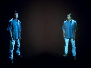 "Film still from Gary Hill's ""Standing Apart"" Two identical men are facing each other."