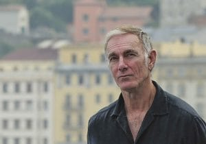 John Sayles standing in front of a cityscape.