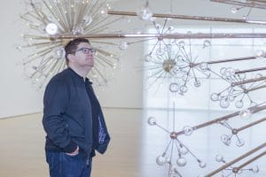 Josiah standing among his glass sculptures