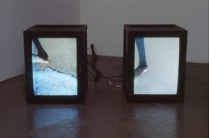 "Janine Antoni's video piece ""Migration"". There are two tv's on the floor. Each tv has footage of a couple walking on the beach."