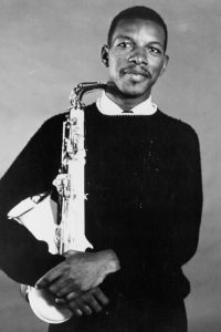 Ornette Coleman smiling and holding a saxophone.