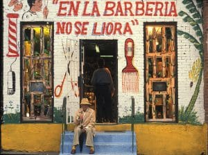 "Barbershop store front installation by Pepon. Red text"" En La Barberia No Se Llora""."