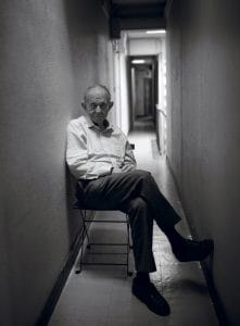 Frederick Wiseman sitting in a chair in a narrow hallway
