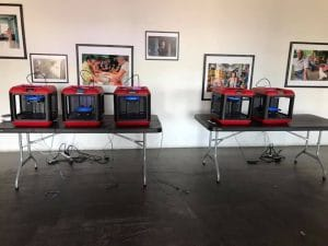 Two tables with 3D printers in the middle of Real Arts Ways gallery