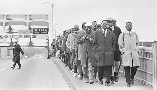 John Lewis marching over the Edmund Pettus Bridge