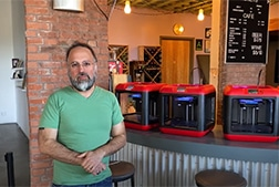 Ian Ally-Seals standing in front of 3D printers in RAW cafe.