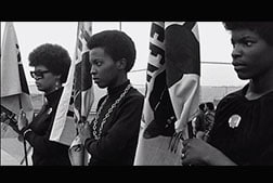 "3 woman standing with flags from Nelson's documentary ""The Black Panthers: Vanguard of the Revolution""."