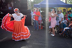A woman dancing in the sunlight while wearing a ruffled orange and white skirt