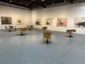 distanced tables and chairs set up in the gallery