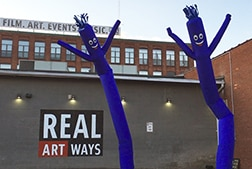 2 purple inflatable tube men in front of Real Art Ways