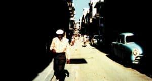 A man walking down a sunlit street