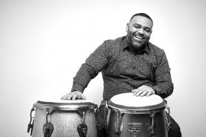 Nelson Bello smiling in front of drums.