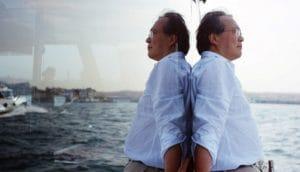 Yo-Yo Ma on a boat, his reflection mirrored in the boat's window
