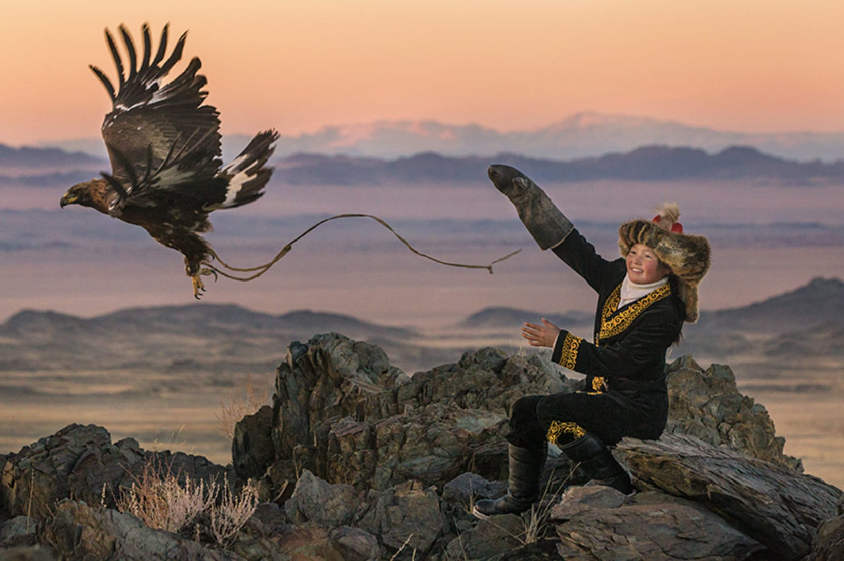 Eagle Huntress with an arm outstretched and an eagle flying away.