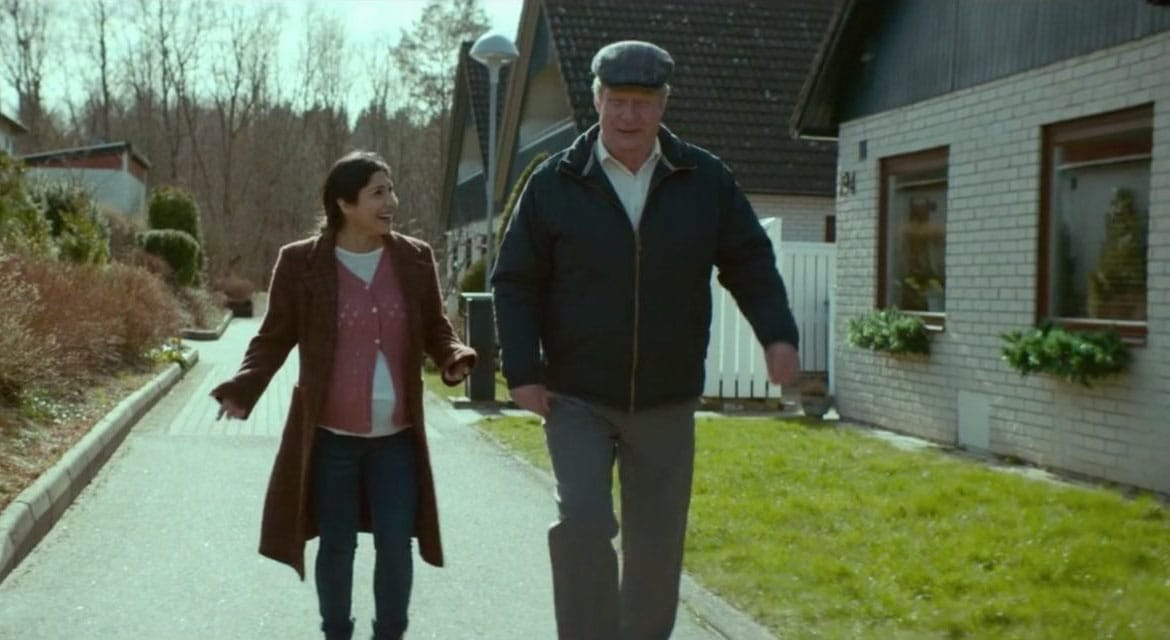 """A man and woman walking while in conversation, from """"A Man Called Ove."""""""
