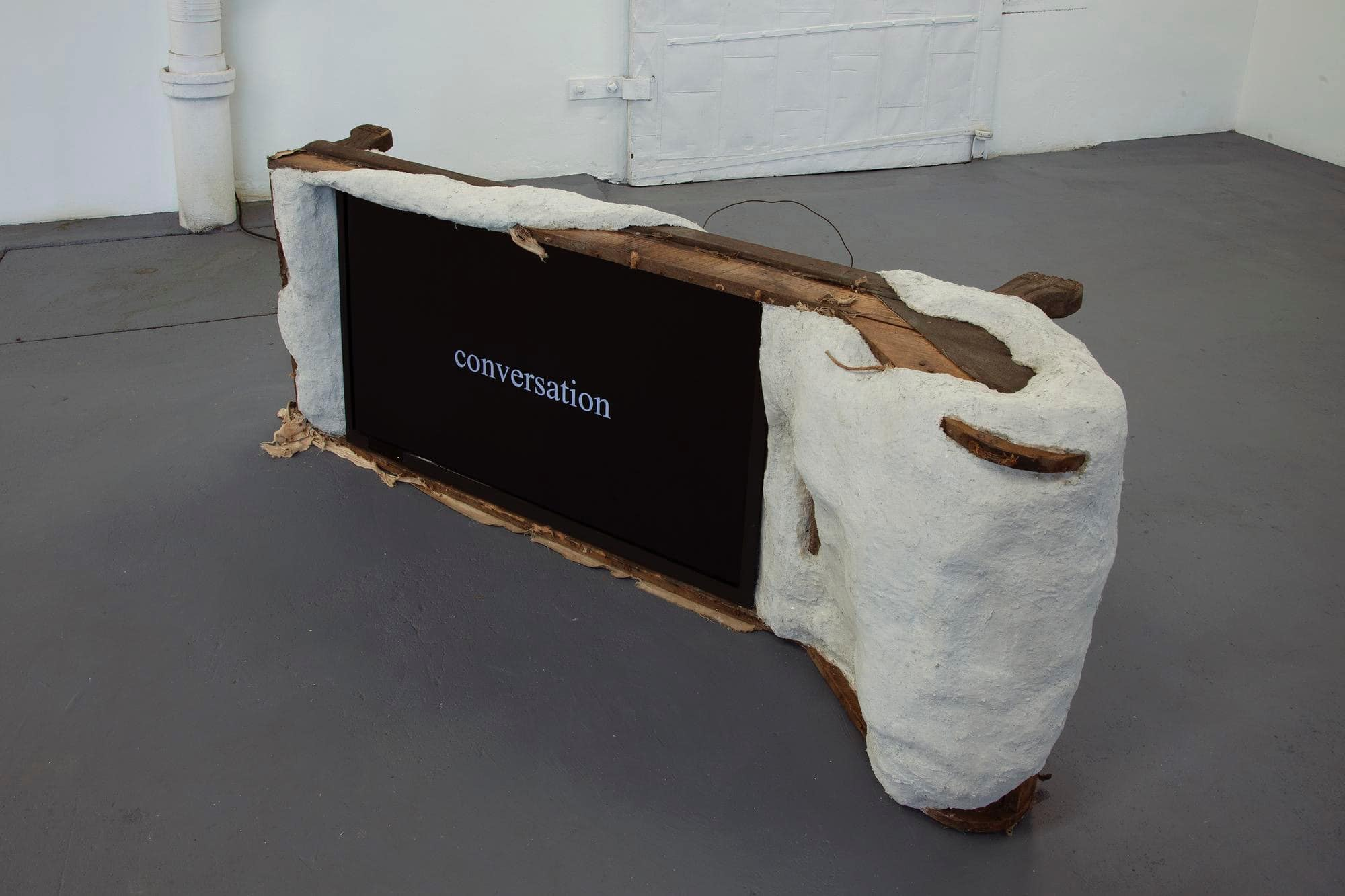 """A television screen with a ceramic and wire hand made frame. On the screen is the text """"conversations"""""""