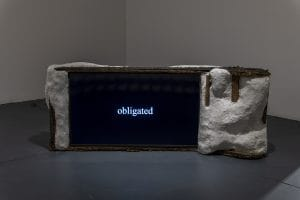 """A television screen with a ceramic and wire hand made frame. On the screen is the text """"obligated"""""""
