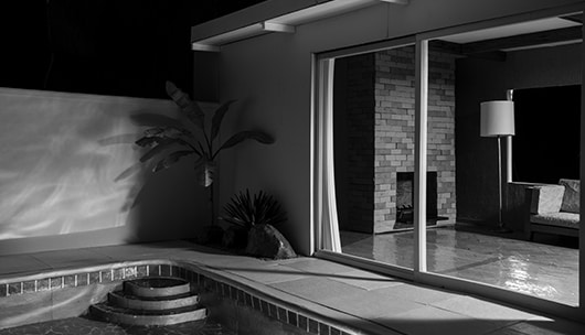 Black and white photo of an outdoor pool and sliding glass door of a house, everything in the photo is a miniature model constructed by the artist