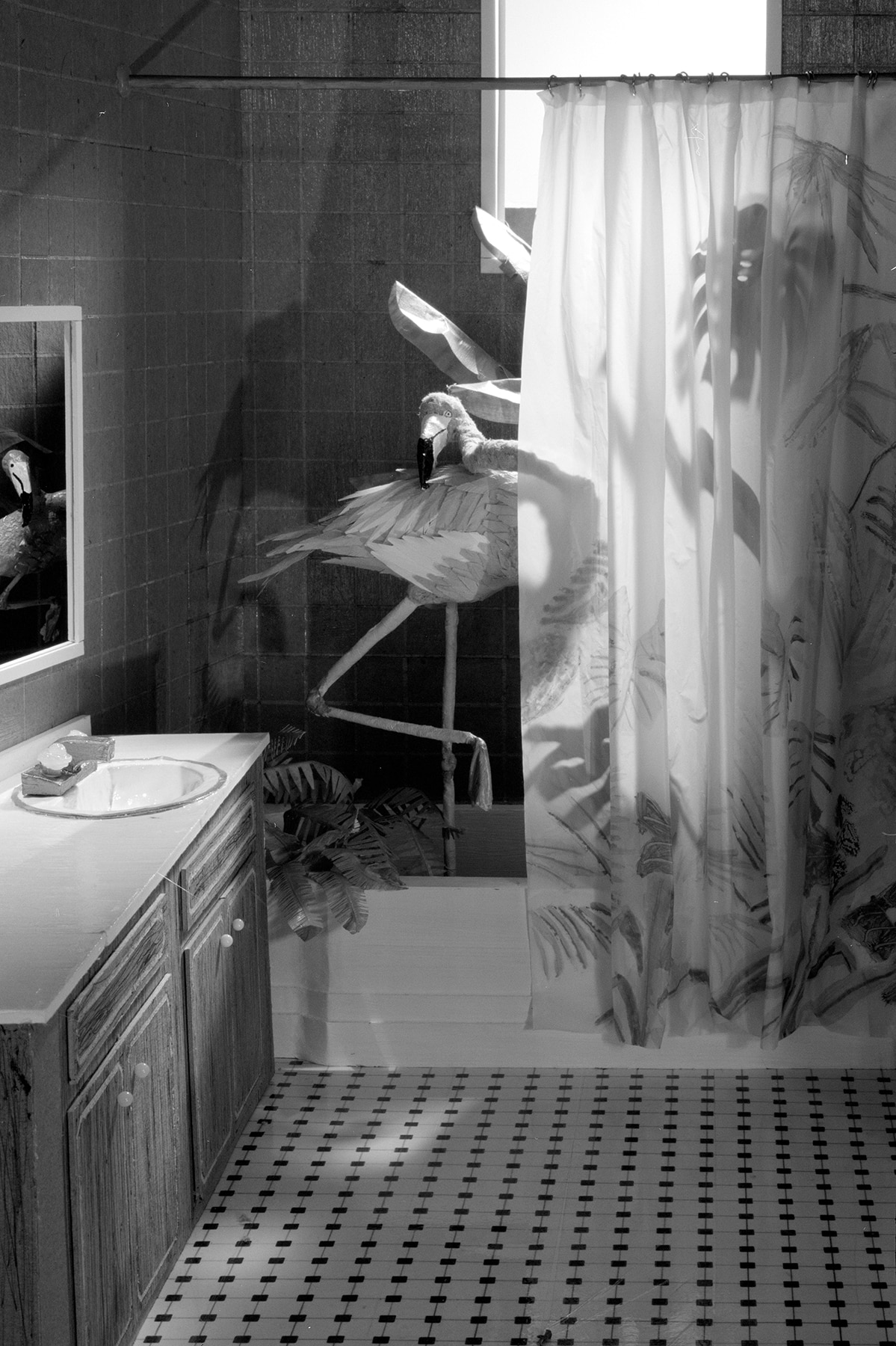 Black and white photo of a fake flamingo in a shower, everything in the photo is a miniature model constructed by the artist