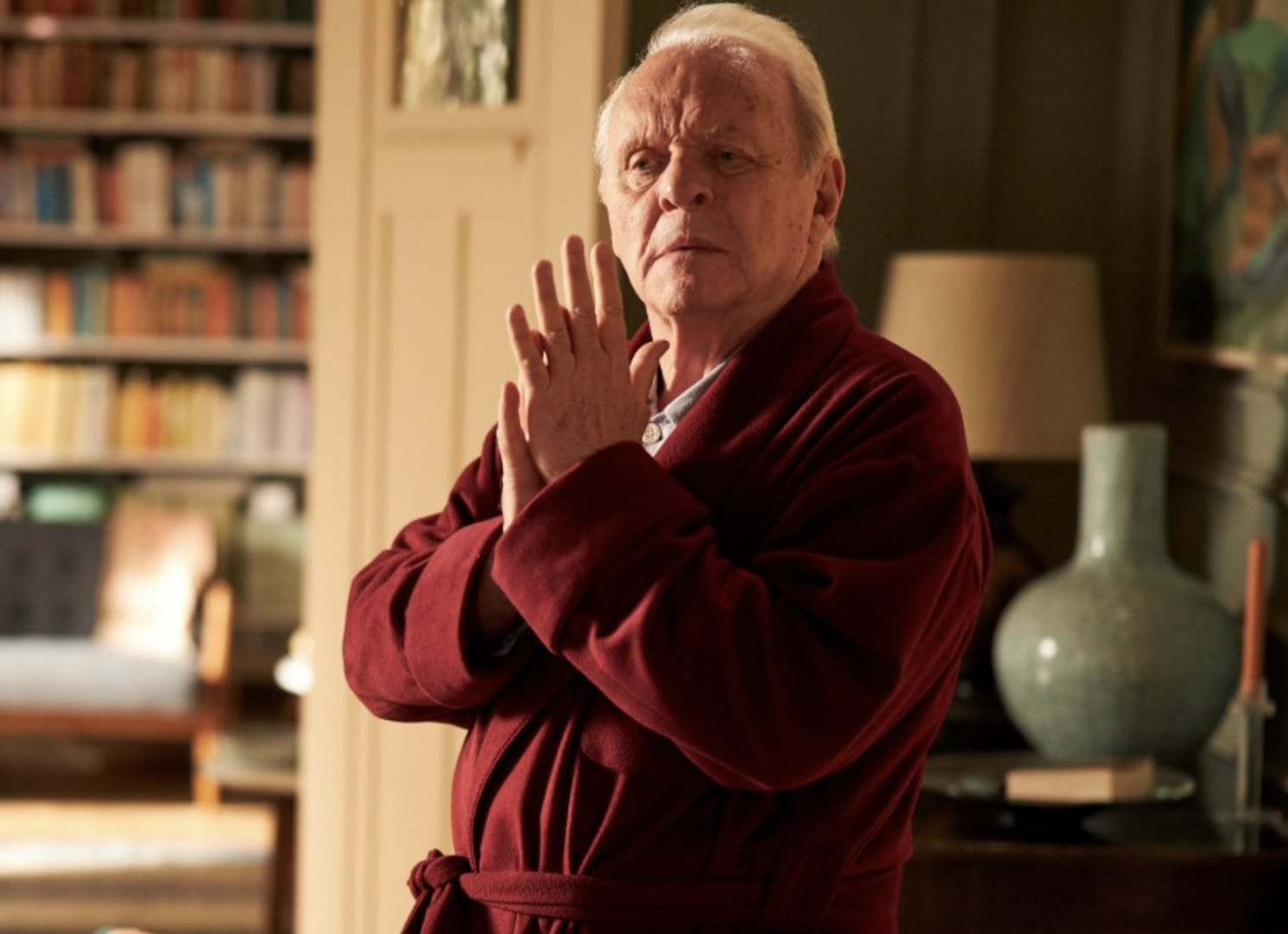 Anthony Hopkins in The Father, wearing a red bathrobe over pajamas in a living room