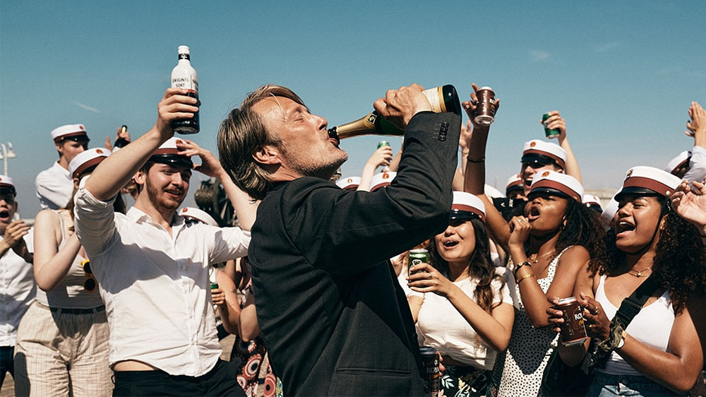 Mads Mikkelsen lifting a glass in a cheering crowd in Another Round