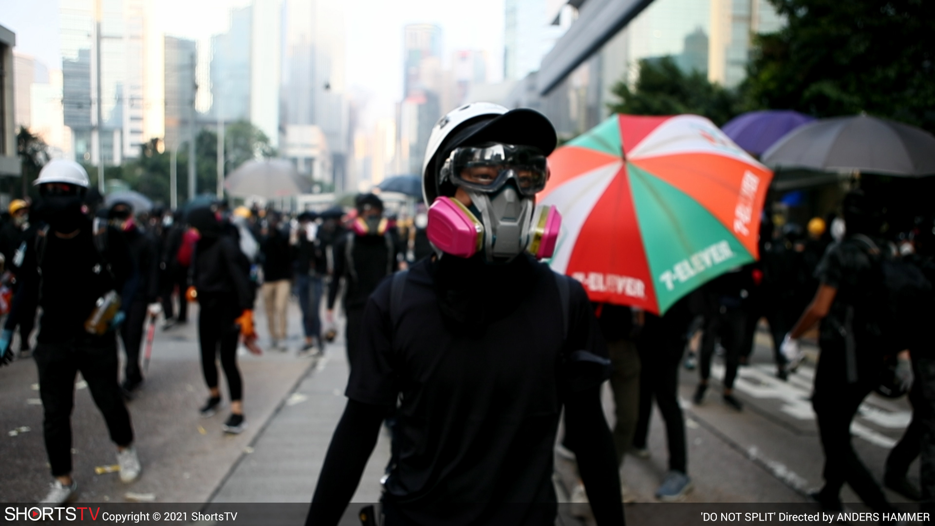A group of people outside in the streets. One person clearly visible is wearing a gas mask.
