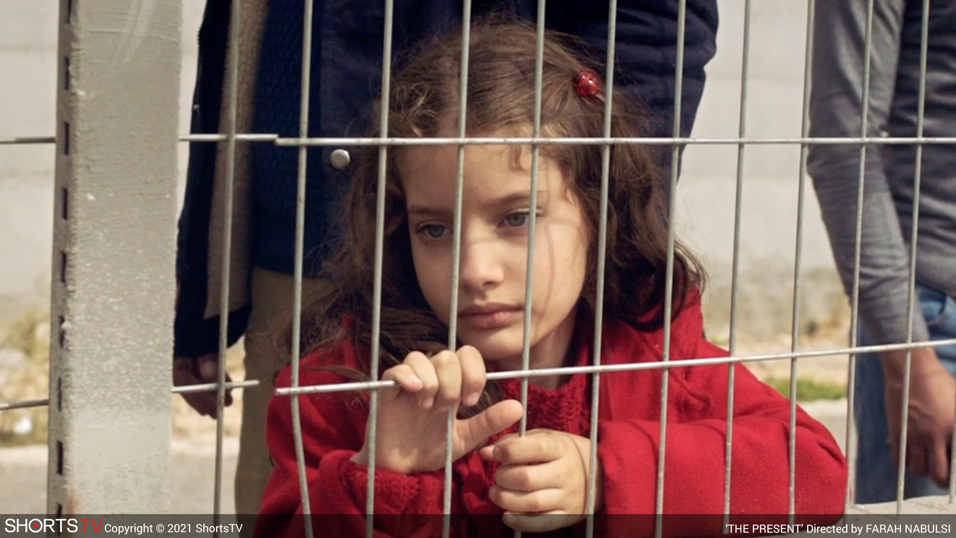 A girl in a red coat behind a fence