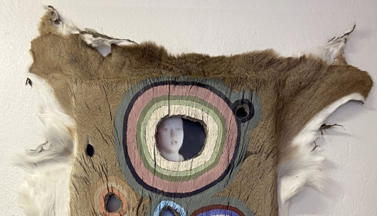 A brown animal pelt is stretched over a frame then painted with circular forms, with holes revealing a photograph of Kyle Rittenhouse underneath the pelt