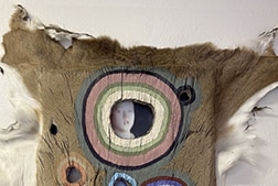 An animal pelt with a hole in it and behind the hole is an image of Kyle Rittenhouse
