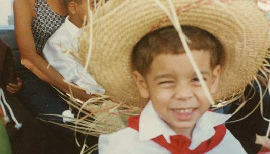 A grainy photograph of a young boy in a straw hat and Puerto Rican jibaro outfit gives a mischievous smile and wink to the camera