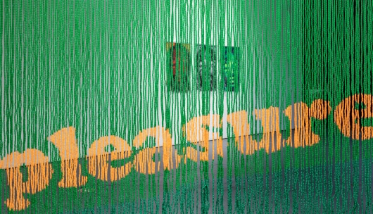 "A green beaded curtain with orange text ""pleasure""."