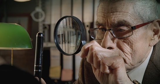An older man looking in a magnifying glass, The Mole Agent