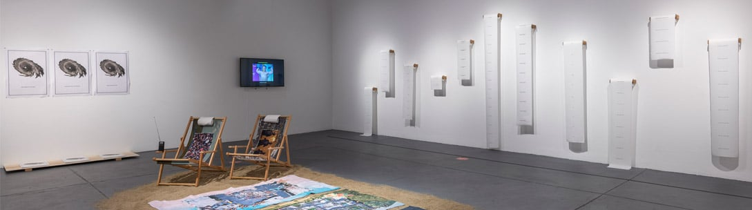 Installation image of Kevin Quiles Bonilla's solo exhibition with beach chairs sand and beach towels on the gallery floor and paper towels on the walls