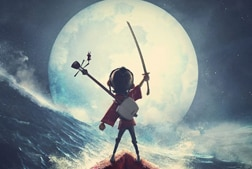 Animated still from Kubo and the Two Strings with a young boy raising a sword in front of a full moon